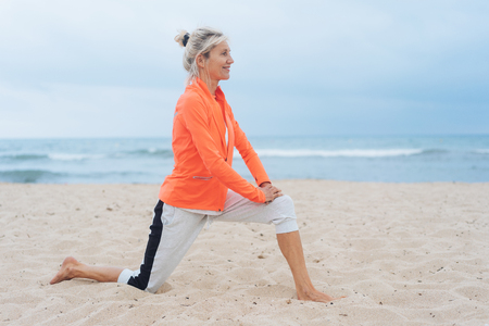 Active healthy blond woman doing stretching exercises on a sandy tropical beach on a hazy day in a close up profile view Stock Photo