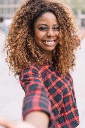Happy charismatic young African woman in a red plaid shirt holding out her arms grinning at the camera in an urban street