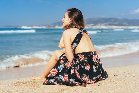 Young woman enjoying the sunshine at the beach sitting on the sand in a floral dress gazing out to sea with a smile Stock Photo
