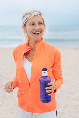 Blond woman exercising on a beach carrying a blue bottle of water looking to the side with a beaming happy smile