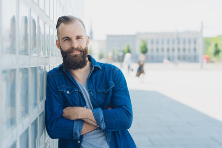 Confident young bearded man in casual denim leaning on a glass brick wall in a quiet high key city square looking at the camera