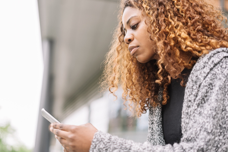 Side portrait of pretty young black woman outdoors with mobile phone. Stock Photo