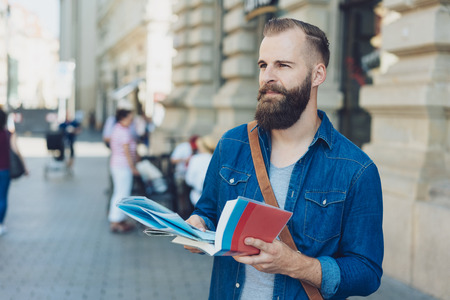 Thoughtful bearded man sightseeing with a map and guide book while travelling on his summer holiday standing in a city street looking to the side