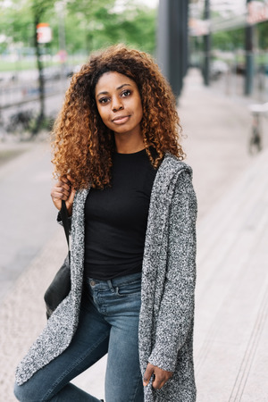 Street portrait of young African American woman wearing grey sweater