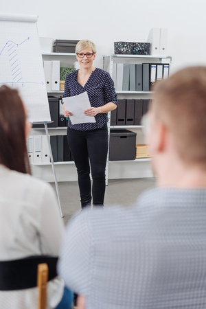 Businesswoman or team leader giving a talk or presentation during a meeting at the office in an over the shoulder view