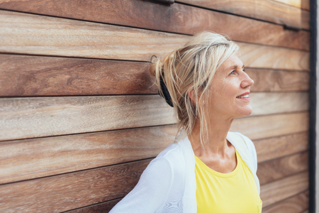 Attractive mature blond woman standing against on oblique angle wooden wall daydreaming and looking up with a quiet happy smile