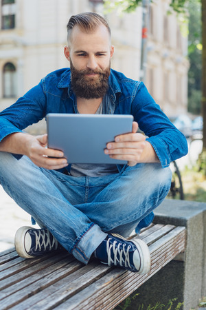 Cool handsome young man wearing blue jeans and denim shirt while using a tablet outdoors in the city