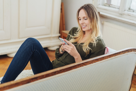 Attractive slender blond woman relaxing on a sofa with her mobile phone reading a text message with a smile
