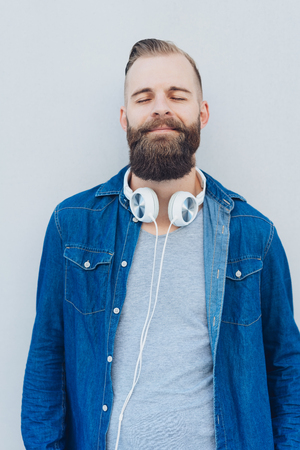 Blissful man relaxing listening to music through stereo headphones around his neck as he stands leaning against a wall with eyes closed smiling