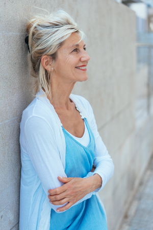 Smiling relaxed middle-aged blond woman with folded arms standing leaning on a receding exterior wall looking up with a happy expression