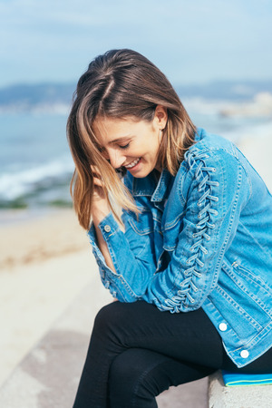 Attractive trendy young woman in a denim jacket seated on a bench at the seaside overlooking the ocean looking down with a smile Stock Photo