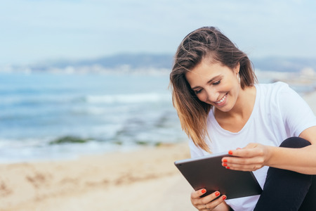 Young woman sitting reading on her tablet pc with a smile on a promenade overlooking a beach and ocean in a close up cropped view