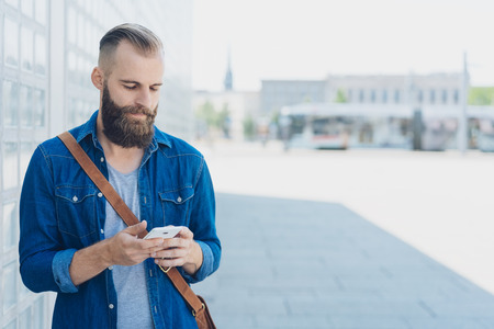 Bearded man reading a sms on his mobile phone as he stands in a high key urban square on a sunny day
