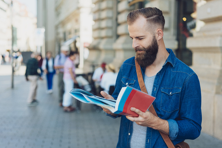 Attractive bearded male tourist standing in an urban street with a guide book and map looking up sightseeing information Stock Photo