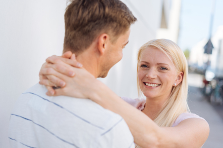 Smiling happy young blond woman hugging her husband or boyfriend with a loving smile outdoors on an urban sidewalk Stock Photo