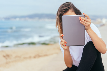 Young woman using a tablet at the seaside with her face hidden behind the screen and back to the ocean with copy space
