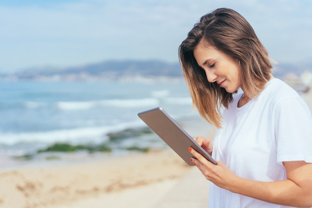 Woman smiling as she uses a tablet pc standing on a promenade overlooking the ocean in a close up profile view Stock Photo
