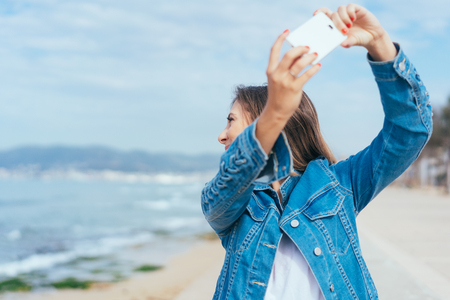 Young woman taking a selfie looking back at the sea as she stands on a beachfront promenade on summer vacation
