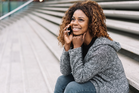 Young African sitting woman chatting on a mobile on a flight of exterior urban steps listening with a smile Stock Photo