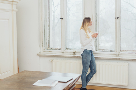 Woman in jeans standing staring out of an office window on a misty day holding a cup of coffee