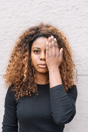 Attractive African woman covering one eye with her hand as she stares calmly at the camera against a rough plaster white wall Stock Photo