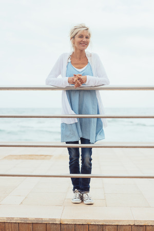 Trendy blond woman standing on a wooden pier leaning on the rails looking out over the sea with a smile