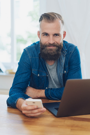 Smiling friendly modern businessman with beard wearing casual denim clothes seated at an office table with a laptop and mobile phone