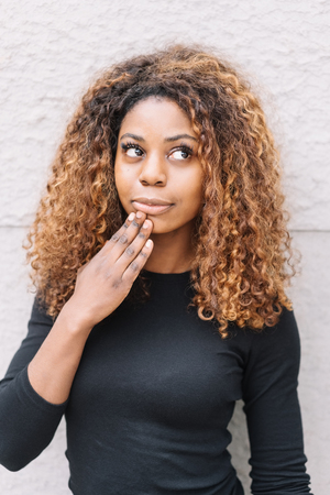 Cute pretty thoughtful young African woman with her hand to her chin looking up to the side with a contemplative expression Stock Photo