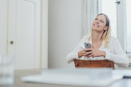 Happy young woman in love sitting holding a mobile in her hands looking up with a blissful smile indoors in a low angle view over a table
