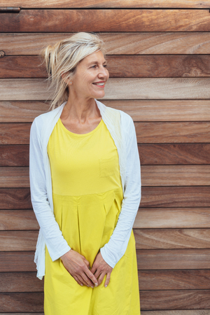 Attractive blond woman in a yellow summer dress standing against a natural timber wall looking to the side with a happy smile