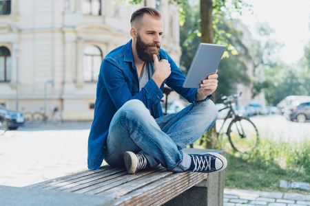 Trendy young man sat on city park bench using tablet with thoughtful expression. Stock Photo