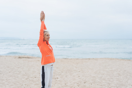 Healthy fit woman doing stretching exercises on a sandy beach on a cloudy day with calm ocean in an active lifestyle concept Stock Photo
