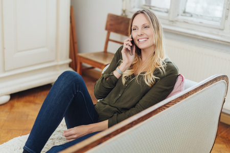 Young woman spending a relaxing day at home sitting on a couch chatting on her mobile phone with a happy smile