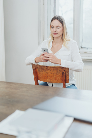 Young woman sitting on a chair text messaging on her mobile phone in front of a light window with table and paperwork in the foreground Stock Photo