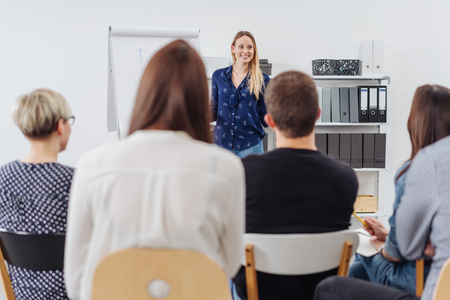 Attractive woman giving a presentation or lecture to a group of people seated with their backs to the camera in an office or classroom