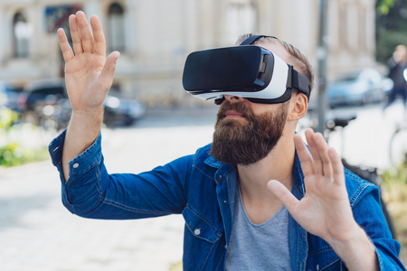 Bearded man outdoors on a city street using a 3d virtual reality headset gesturing with his hands as he interacts with his environment