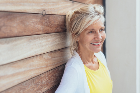 Attractive elderly blond woman with a lovely smile standing looking to the side of the frame leaning against a wooden wall with copy space