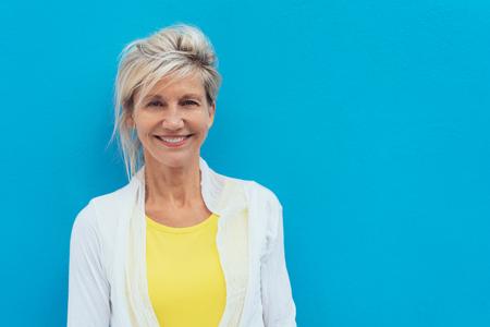 Feliz vivaz mujer rubia mayor en un colorido top amarillo posando contra una pared azul brillante con espacio de copia Foto de archivo