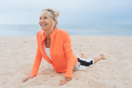 Woman working out on a sandy beach doing press-ups with a smile and ocean backdrop