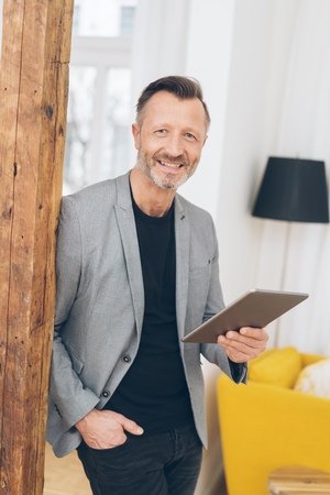 Smiling friendly trendy professional middle-aged man leaning against a wooden pillar in his apartment holding a tablet computer