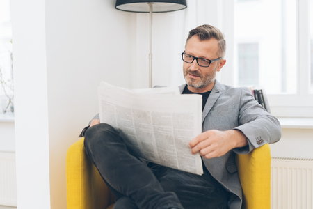 Portrait of mature man wearing glasses reading newspaper while sitting in yellow armchair