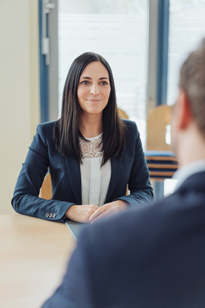 Smiling businesswoman listening attentively during a meeting with a male colleague in an over the shoulder view