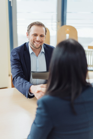 Businessman shaking the hand of a woman with a welcoming smile during a job interview as he holds her CV Фото со стока