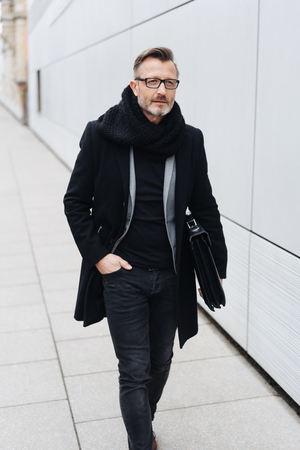 Street portrait of mature man wearing black coat walking with briefcase along sidewalk