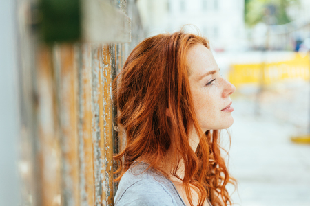 Thoughtful young woman with tousled red hair leaning against an urban wall staring ahead in a close up profile view on a high key background
