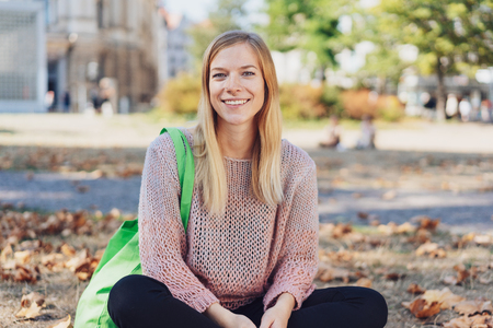 smiling young woman sitting on the street in the city in autumn Reklamní fotografie