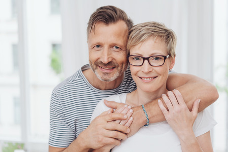 Upper body portrait of affectionate happy middle aged couple, man with arm around shoulder. Banco de Imagens