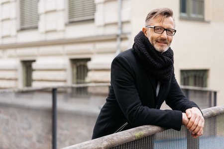 Relaxed businessman in warm coat and scarf standing leaning on a bridge railing in town with a smile 写真素材