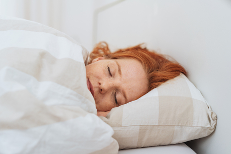 Young redhead woman enjoying a peaceful sleep under a comfortable warm duvet in a close up view of her face