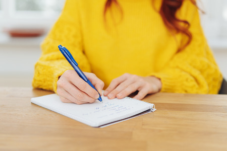 Hands and body of woman in yellow sweater at table writing on notepad.